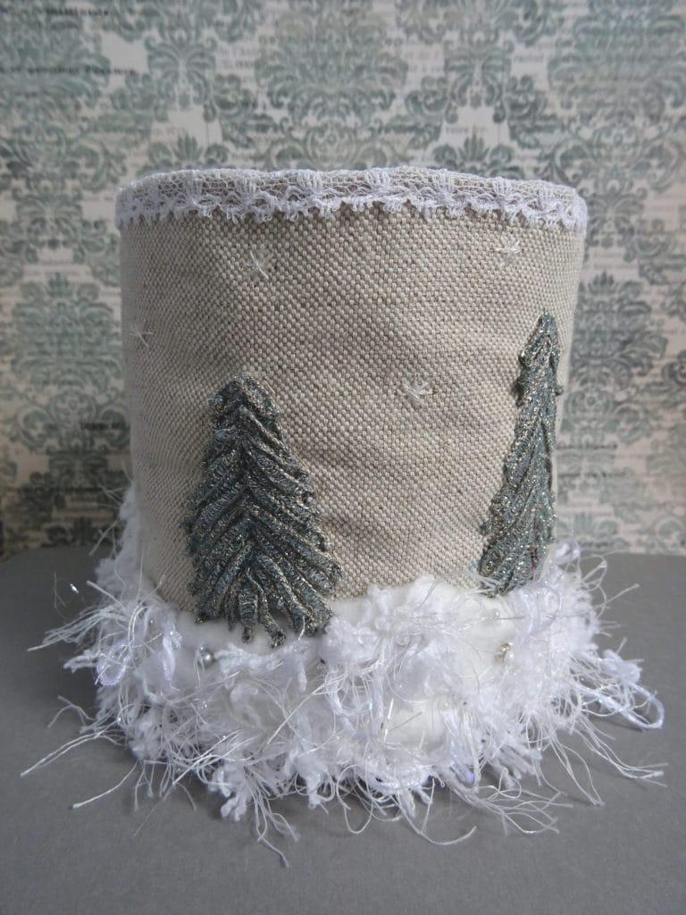 Habillage de boîte proposant un paysage hivernal brodé